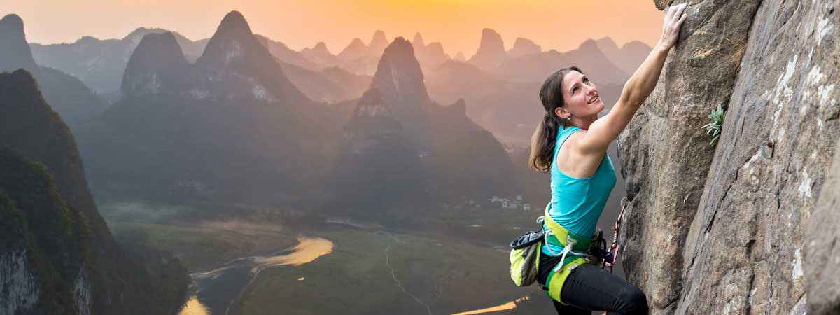 Perseverant Woman Free-Climbing a Vertical Rock Face